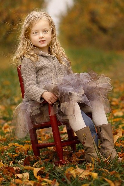 little girl sitting in the fall leaves